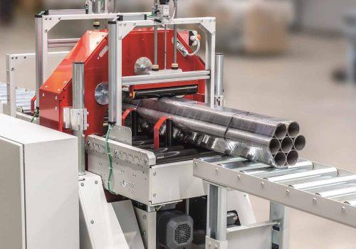 Langgut Einwickelmaschine - Perspektive Rückseite der Maschine mit Förderer und hexagonal angeordneten Stahlrohren als eingewickeltes Produkt