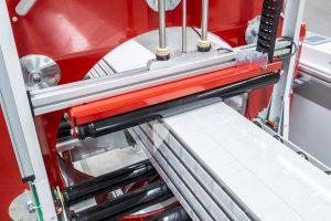 Langguteinwickelmaschine mit Niederhalter während des einwickelns von Kunststoffprofilen